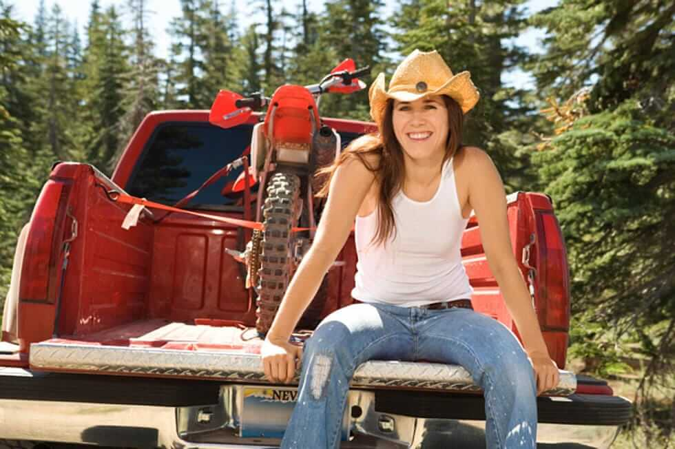 American Girl on tailgate of red pickup truck